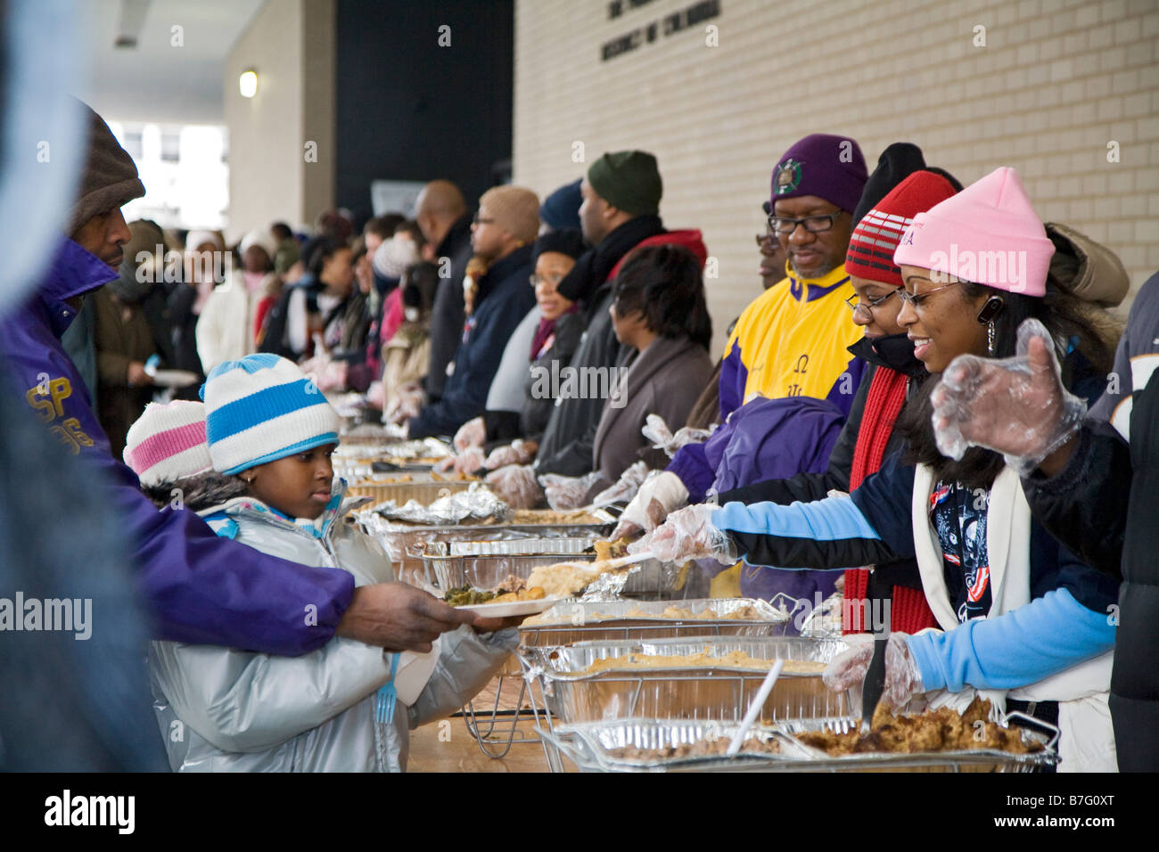 Exceptional Volunteers Serve Meal To The Homeless At Outdoor Soup Kitchen Images