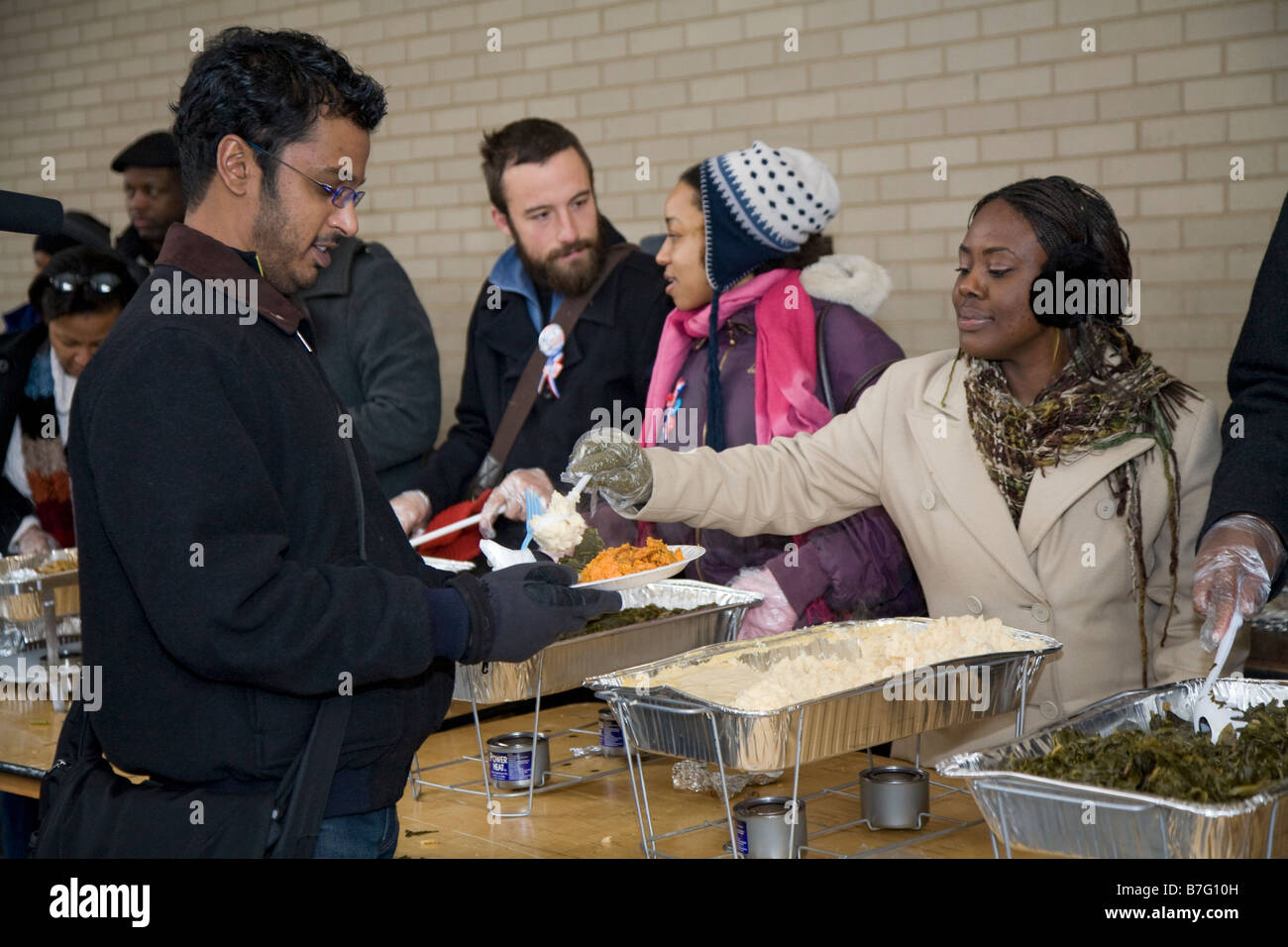 Volunteers Serve Meal To The Homeless At Outdoor Soup Kitchen   Stock Image