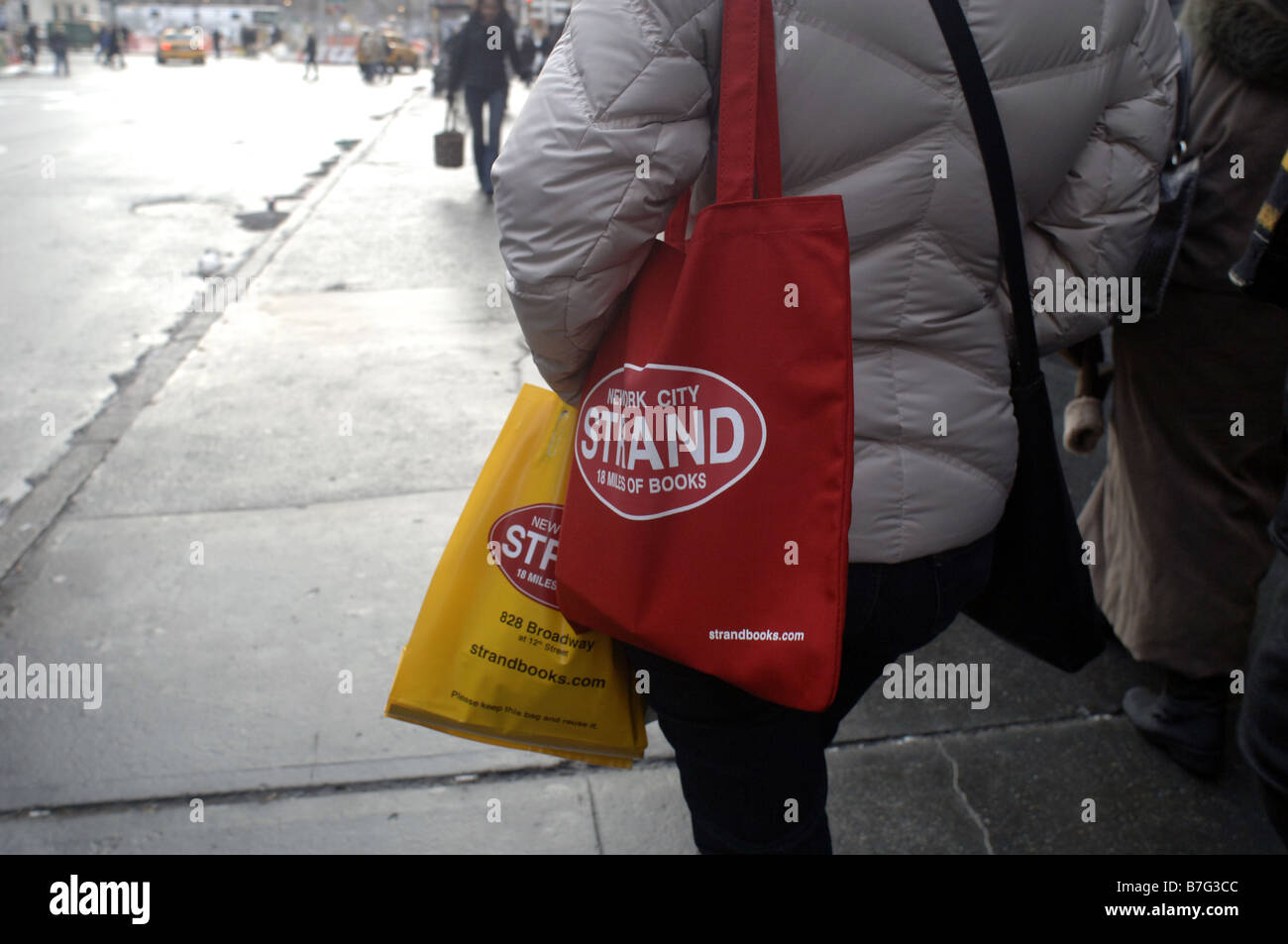 A woman walks down Broadway in the New York neighborhood of the East Village carrying a Strand bookstore tote - Stock Image