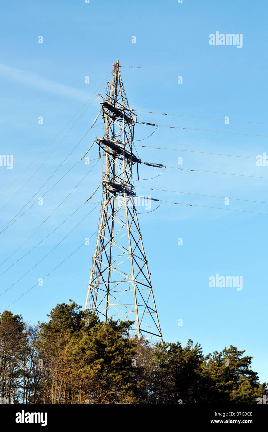 High tension electric tower for transmitting electricity on a hill surrounded by trees Stock Photo