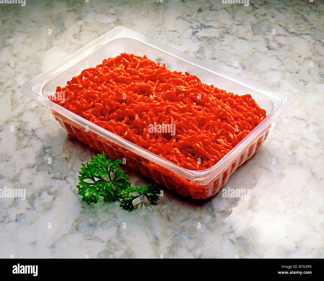 FRESH MINCED BEEF IN A SUPERMARKET PLASTIC CONTAINER , SHOT ON A GREY GRAY MARBLE BACKGROUND WITH A LITTLE PARSLEY - Stock Image