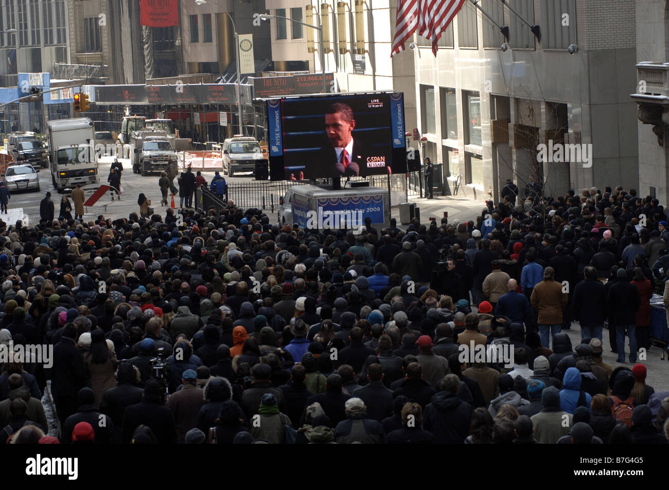 Spectators gather outside the New York Stock Exchange in New York to watch the inauguration of Barack Obama - Stock Image