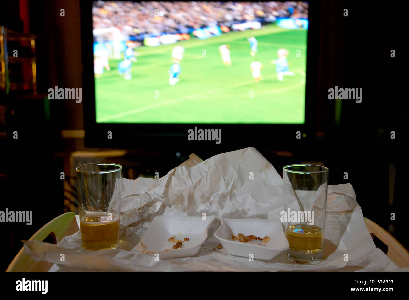 remains of a takeaway meal for two and glasses of beer on a tray in front of soccer on the tv in the living room - Stock Image