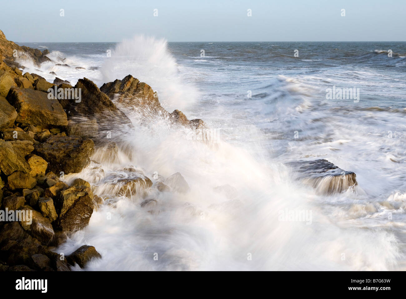 Rough seas crashing against rocks - Stock Image