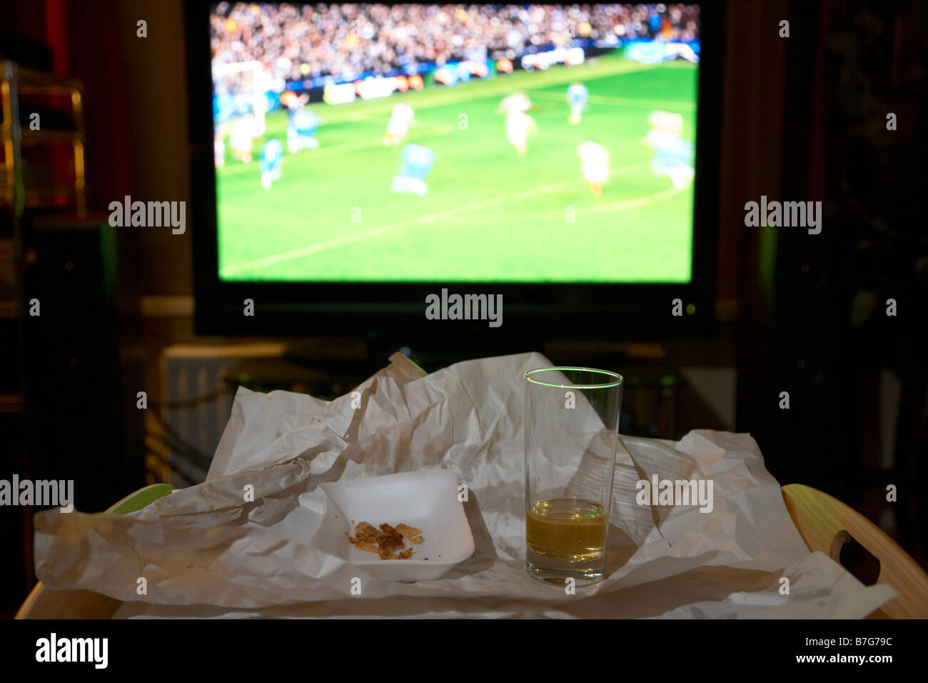 remains of a takeaway meal for one and glass of beer on a tray in front of soccer on the tv in the living room of - Stock Image
