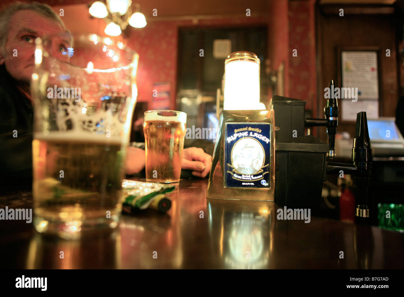 In a London pub, a man at the bar, behind a pint of lager - Stock Image