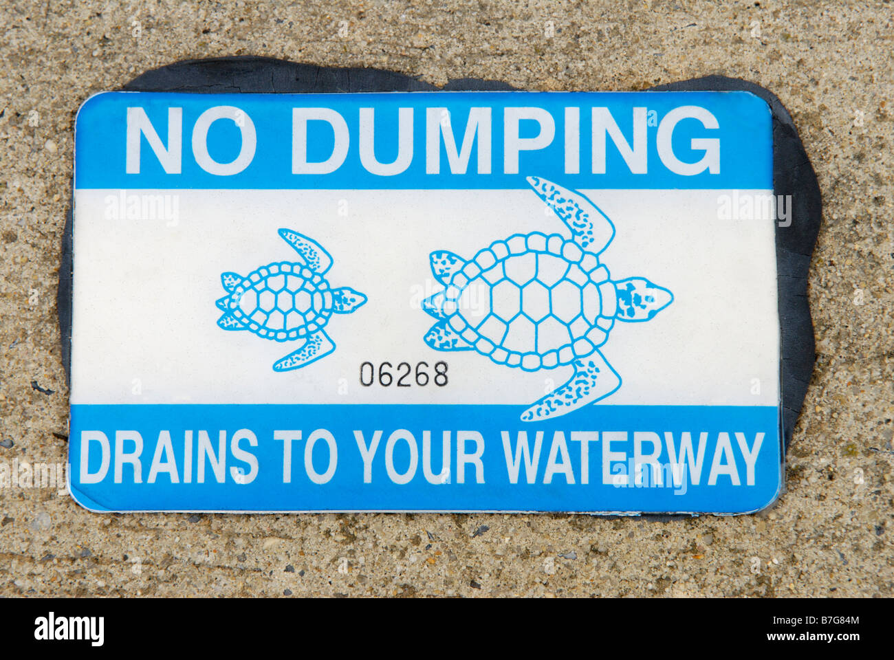 Storm drain decal warning against pollution dumping - Stock Image