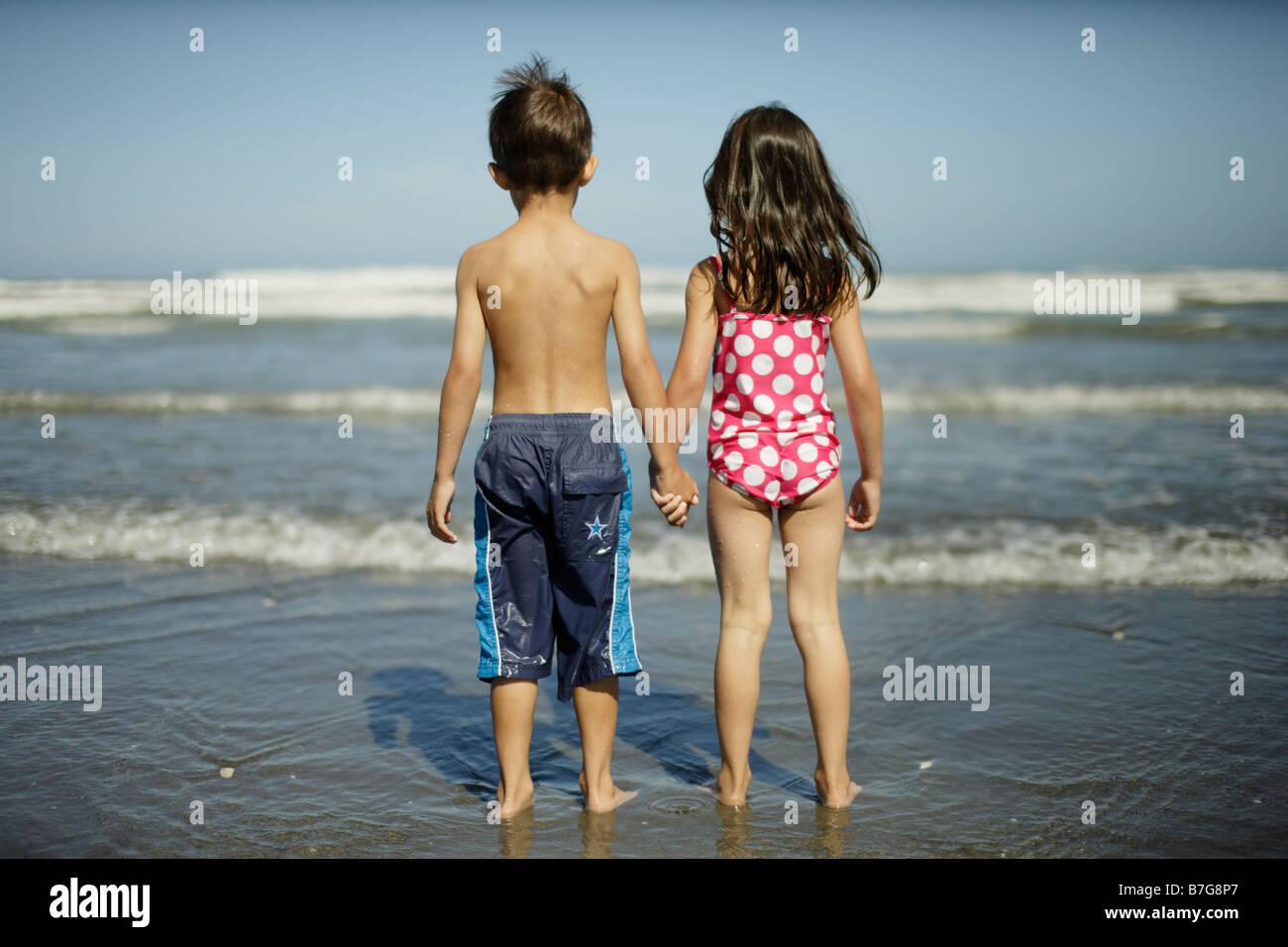 Himatangi beach New Zealand. Girl aged five and boy aged six look out to sea. - Stock Image