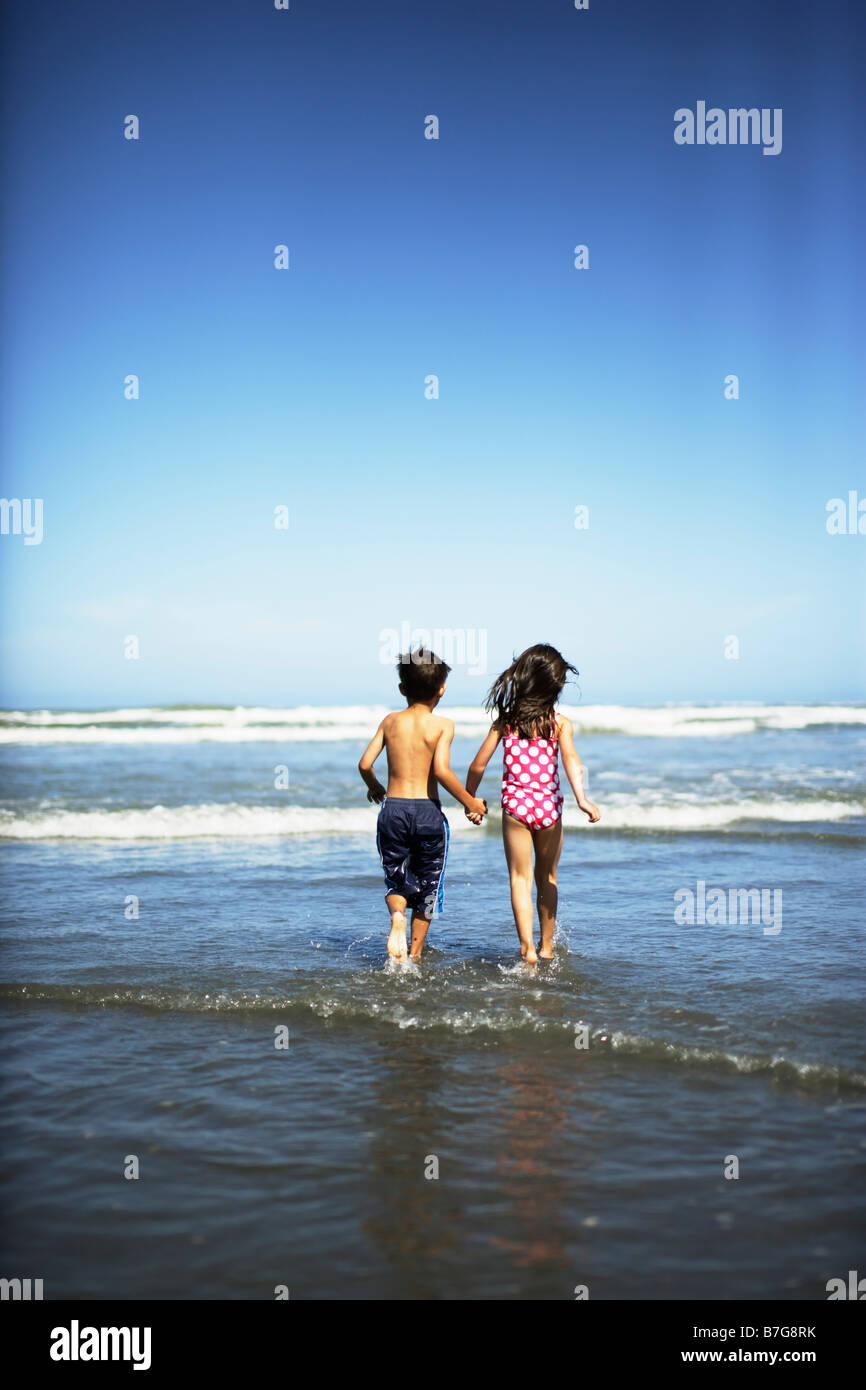 Himatangi beach New Zealand. Girl aged five and boy aged six run into sea. Stock Photo