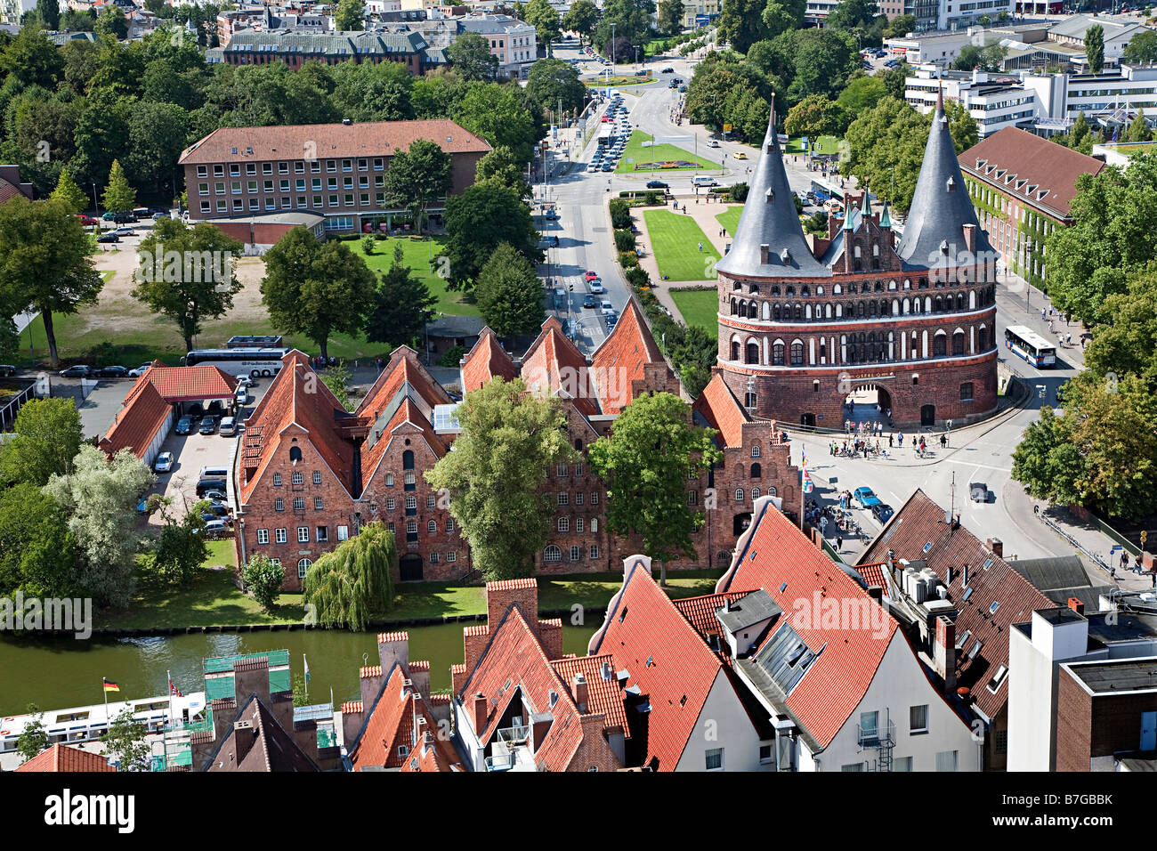 Holstentor city gate and converted salt warehouse Salzspeicher on river Trave Lubeck Germany - Stock Image