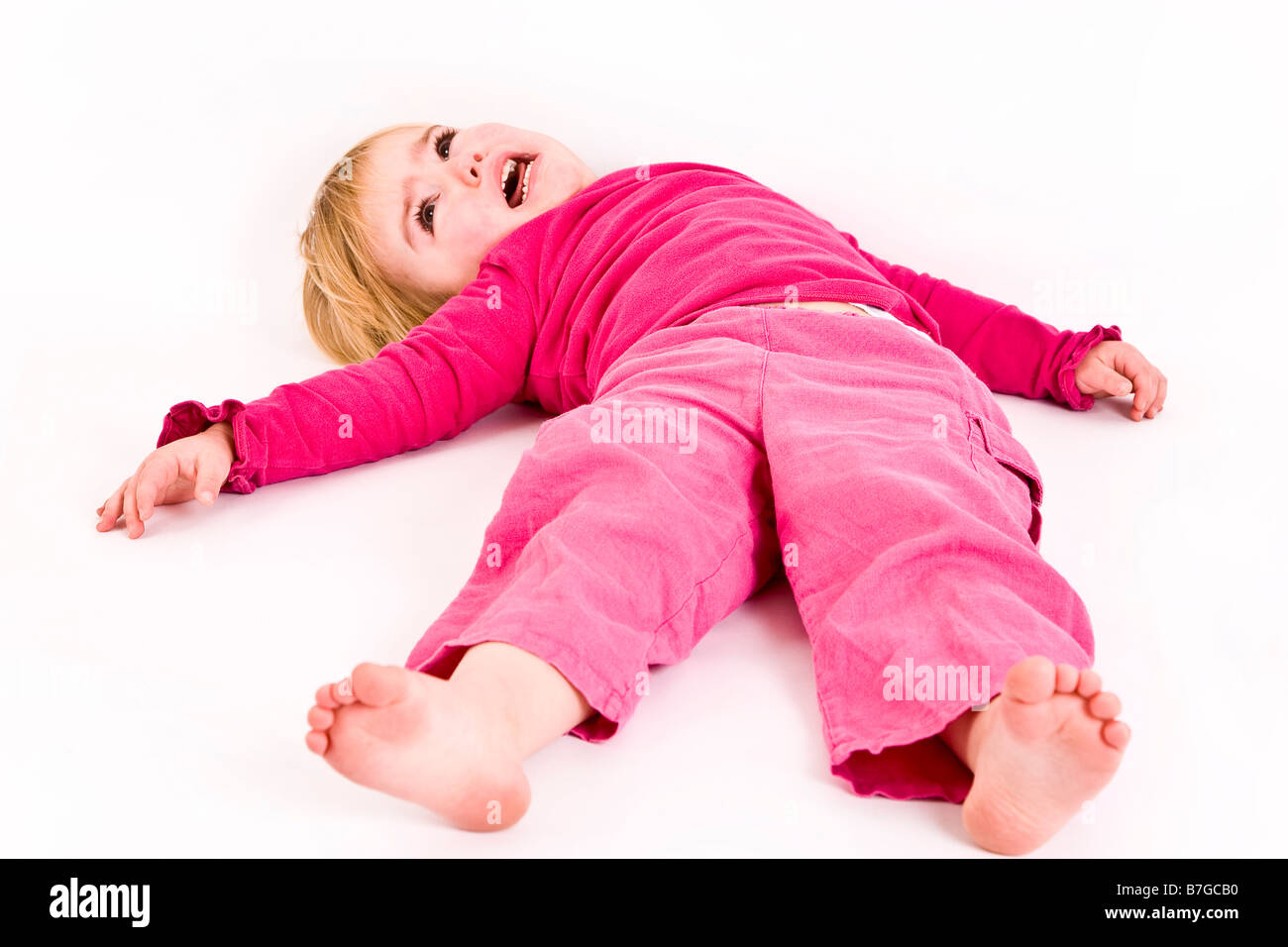 Young female having a temper tantrum on the floor - Stock Image