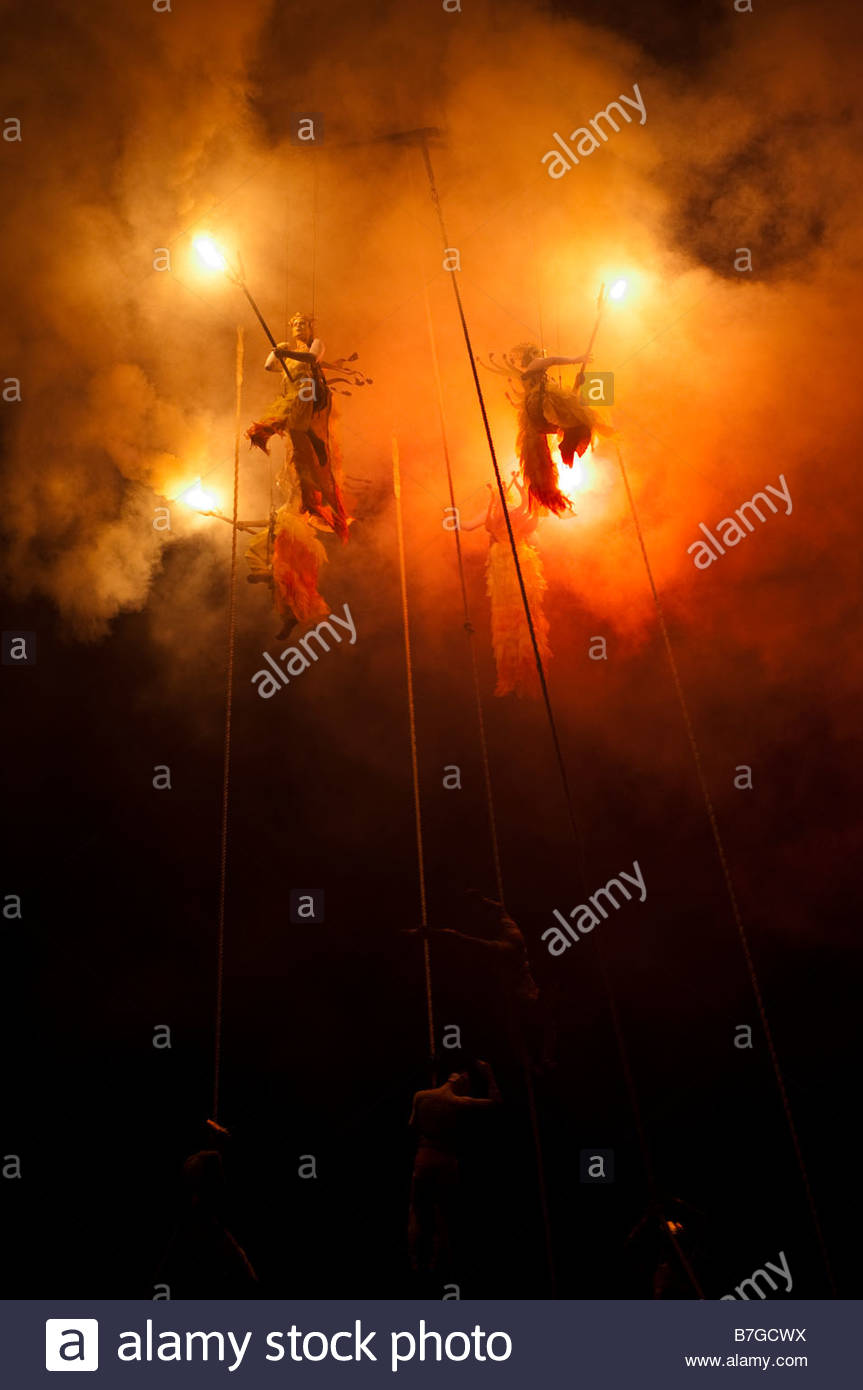 Acrobats and performers hold torches and really bright flares spin suspended from a 250 foot crane All souls procession - Stock Image