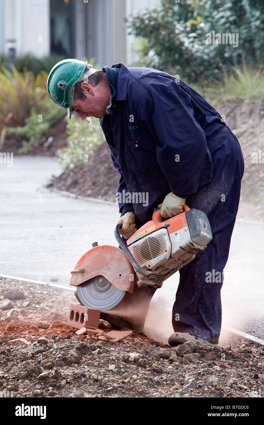 Workman using an Angle Grinder to cut a brick - Stock Image