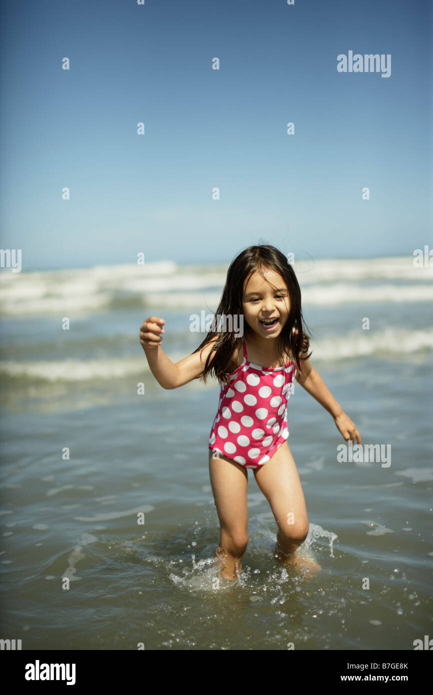 Five year old girl plays in shallow water at Himatangi beach, New Zealand - Stock Image