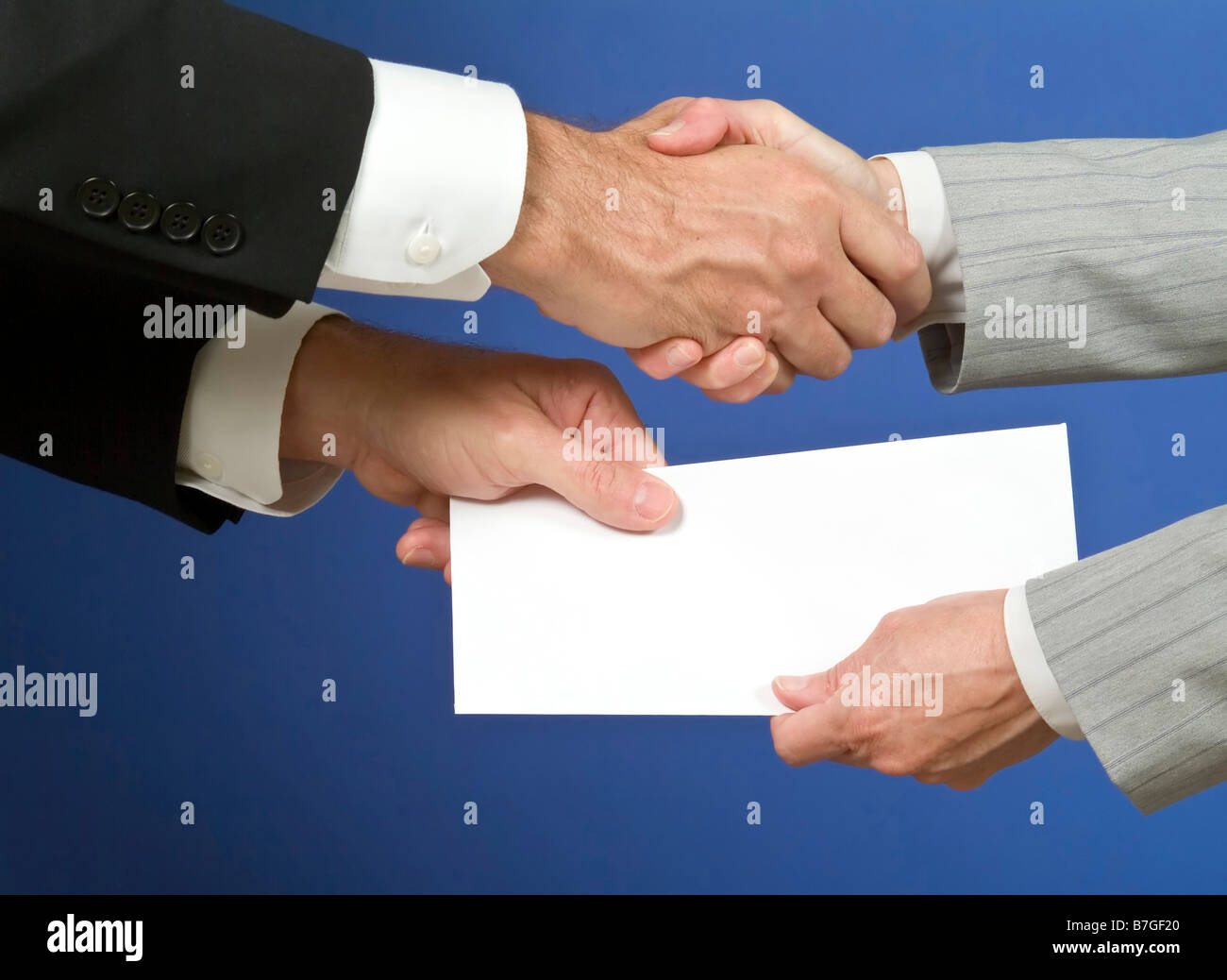 Two people shaking hands and exchanging a white envelope with available copy space for adding text Stock Photo
