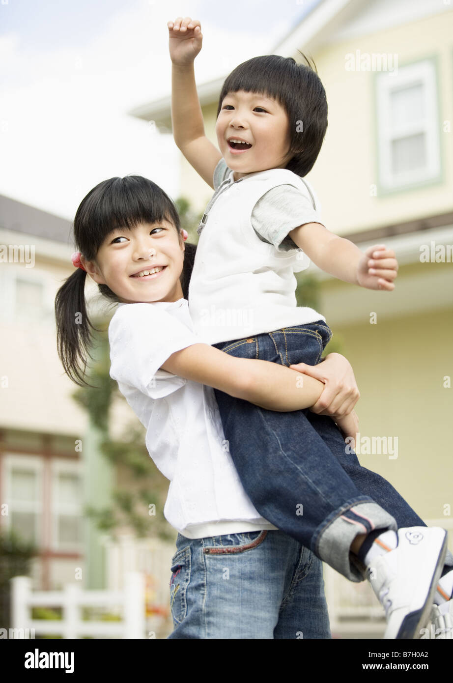 Sister lifting up younger brother Stock Photo