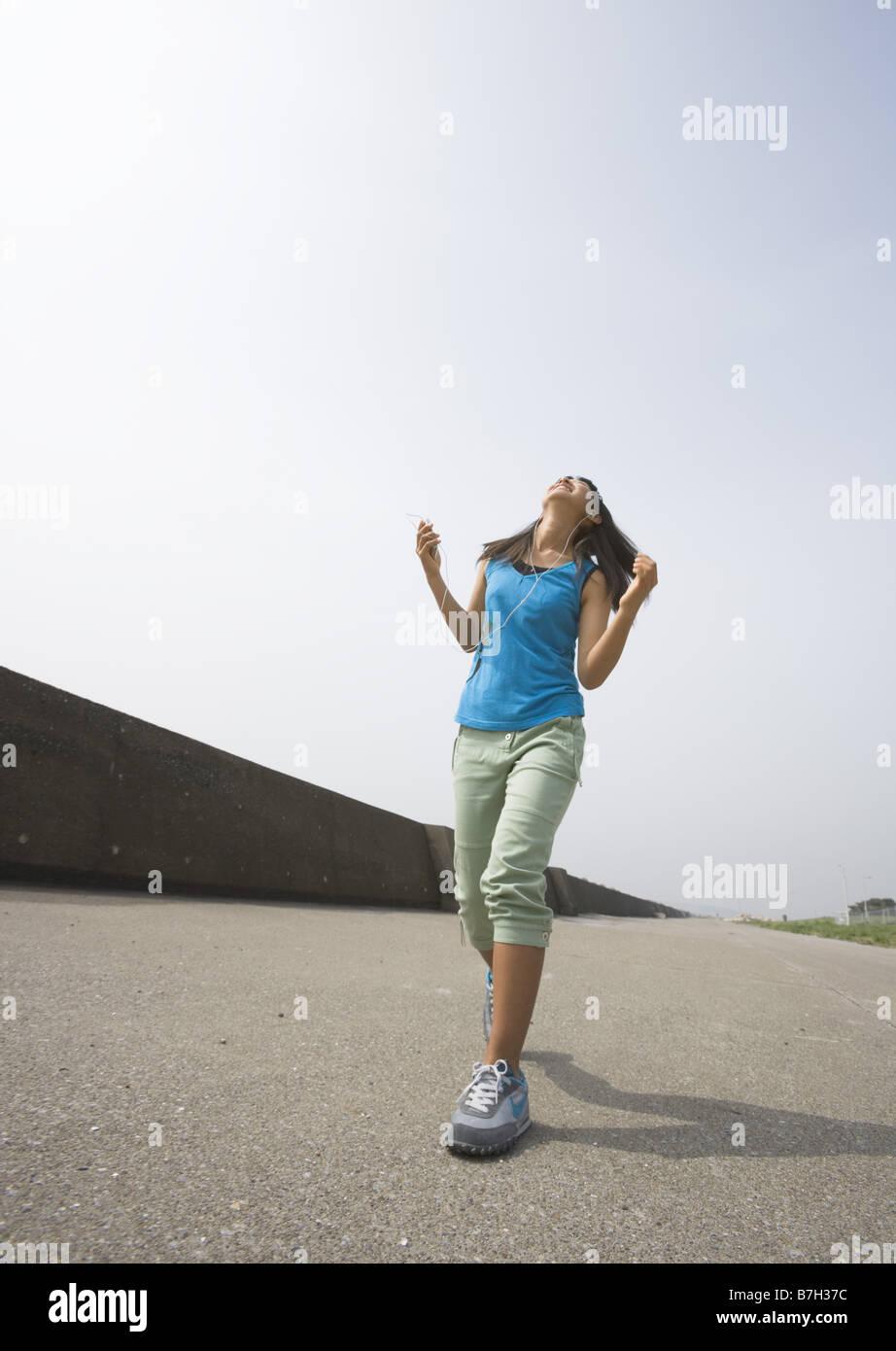 Girl listening to music cheerfully - Stock Image