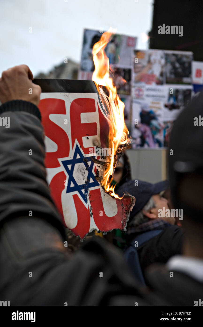 Demonstrators burn the Star of David symbol at a rally to protest against the 2009 Israeli attack on Gaza. - Stock Image