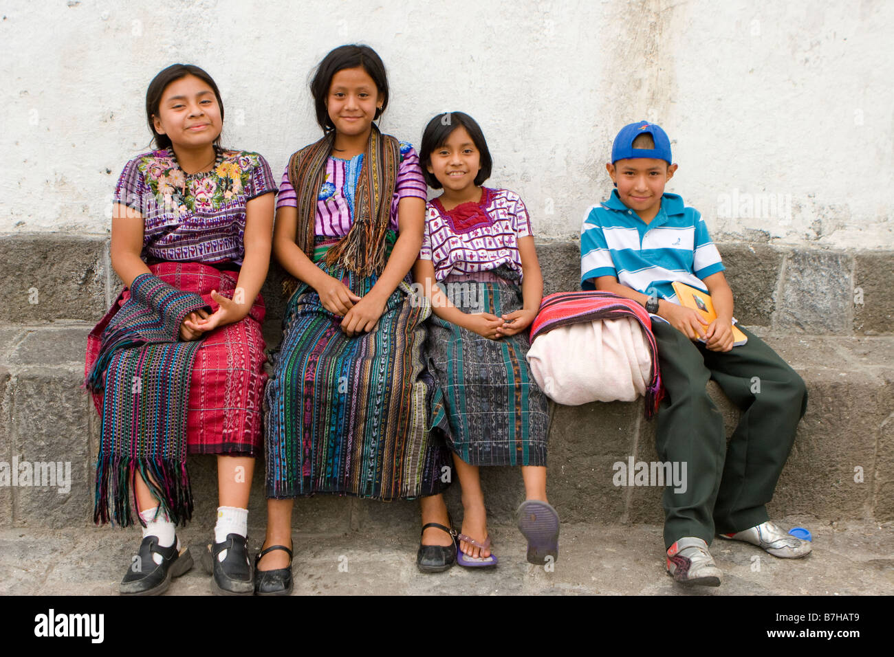 Guatemalan children in traditional dress relax outside a church in Santiago Atitlan, Guatemala - Stock Image