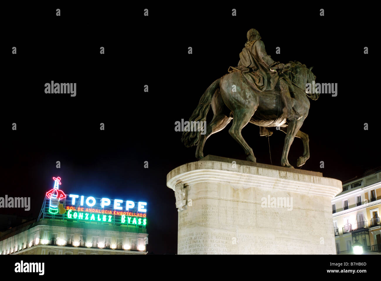 Tio Pepe neon sign and equestrian statue of king Carlos III. Night view. Puerta del Sol. Madrid. Spain. - Stock Image