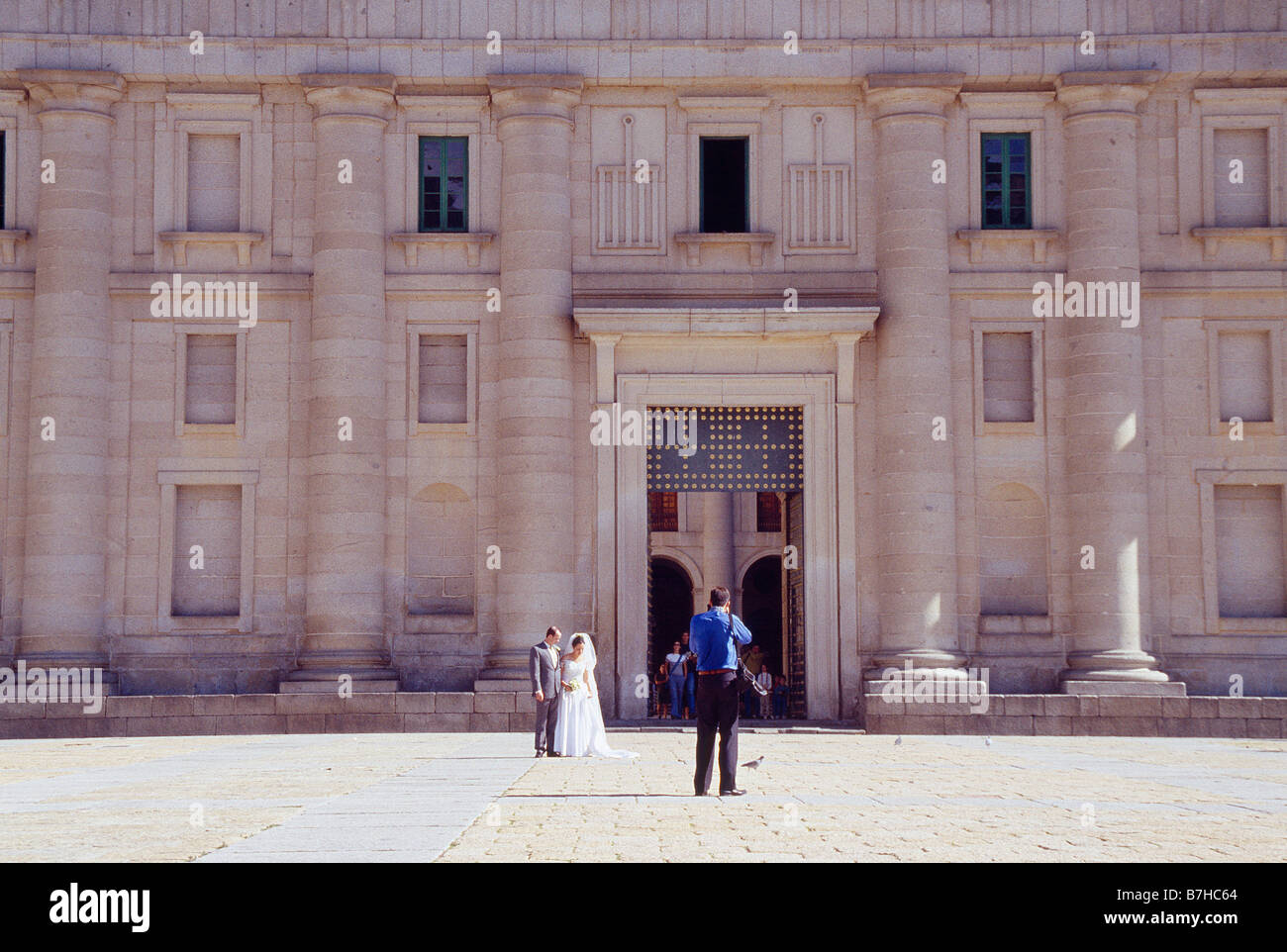 Newlyweds posing in front of the main facade. Monastery of San Lorenzo del Escorial. Madrid province. Spain. - Stock Image
