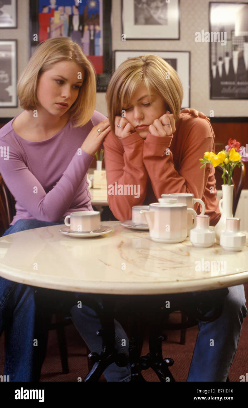 one woman comforting another in a restaurant over a cup of coffee - Stock Image