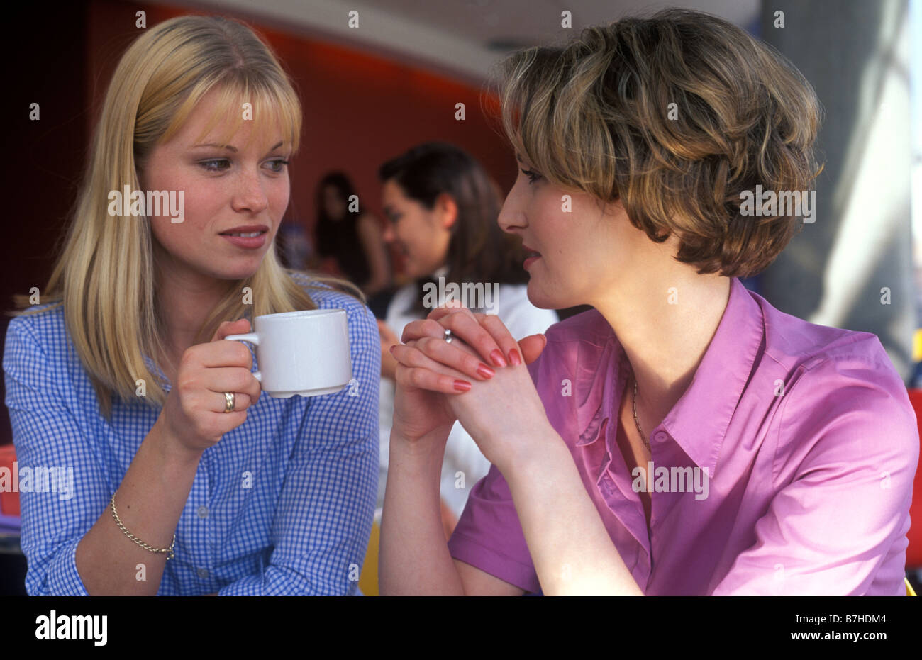 2 women talking seriously over a cup of coffee in a restaurant - Stock Image