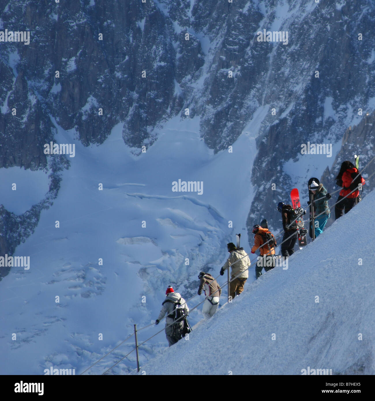 Skiers and boarders make their way down the ice arete, the start of Chamonix's famous Vallee Blanche off-piste - Stock Image
