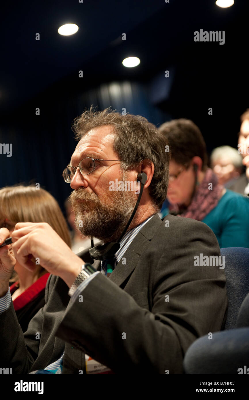 A man delegate at a conference in Wales listening to the debate through simultaneous translation headphones - Stock Image