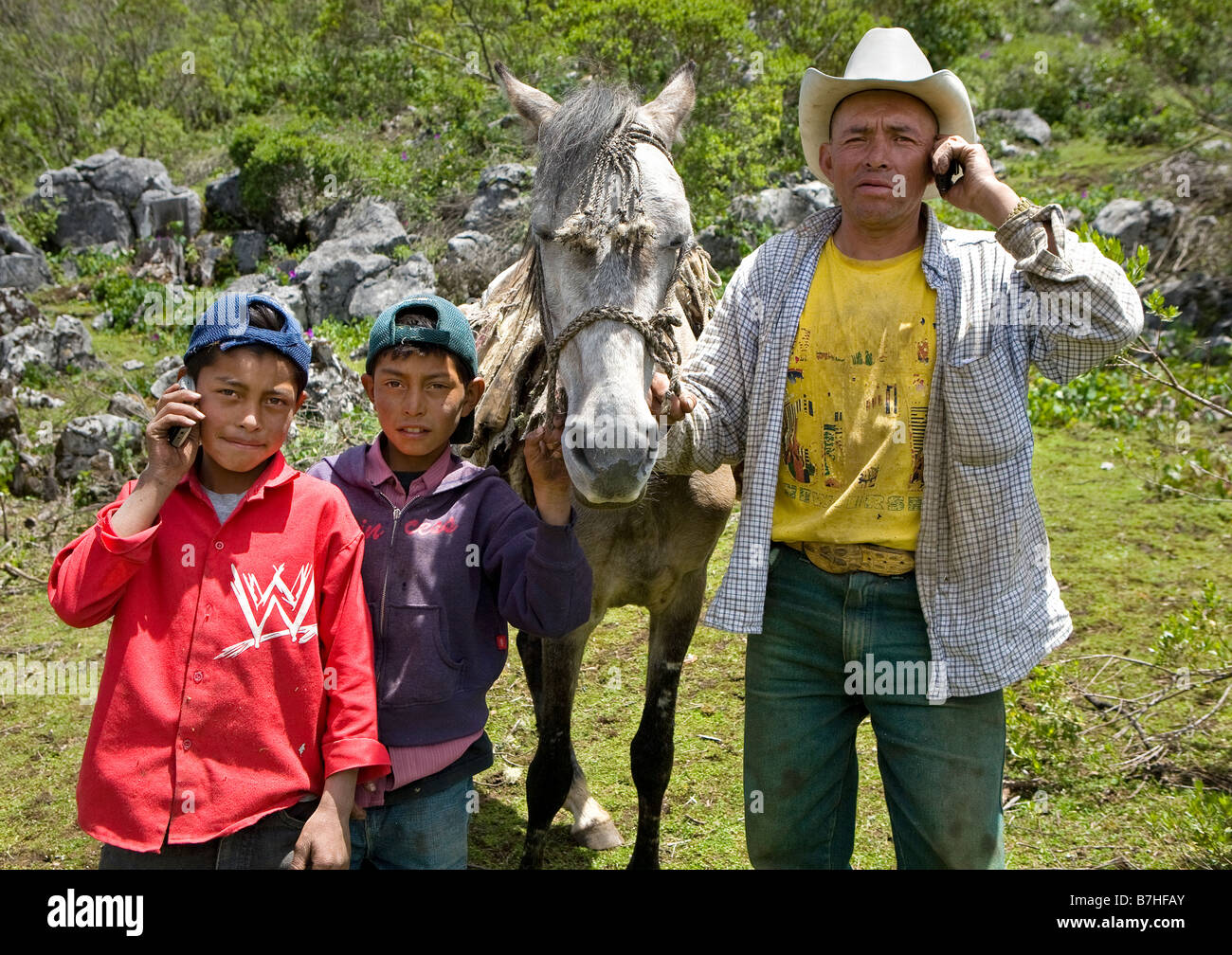 Father and sons posing with cell phones in the countryside near San Nicolas Western Highlands Guatemala Stock Photo