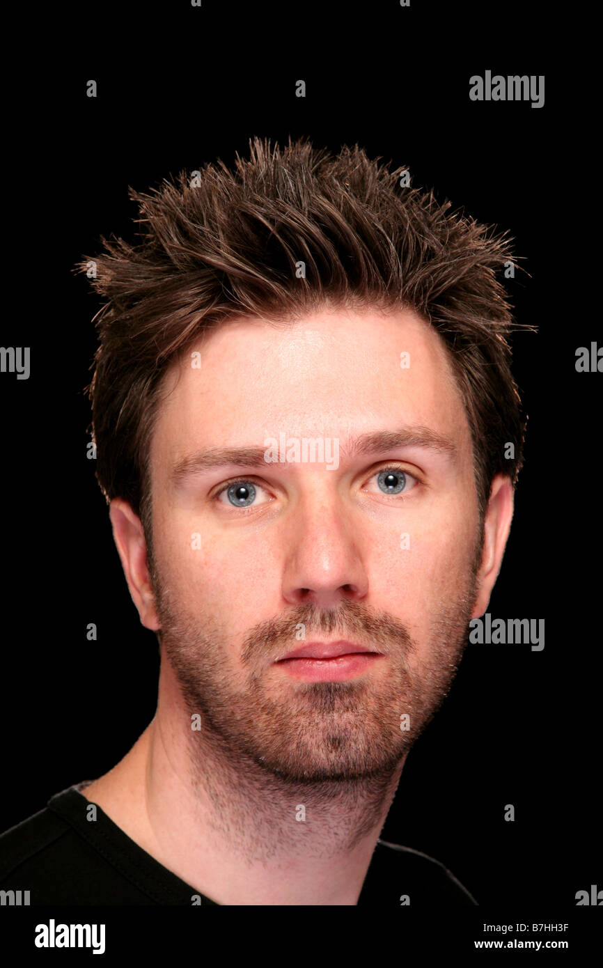 Twenties adult caucasian male on a black background - Stock Image