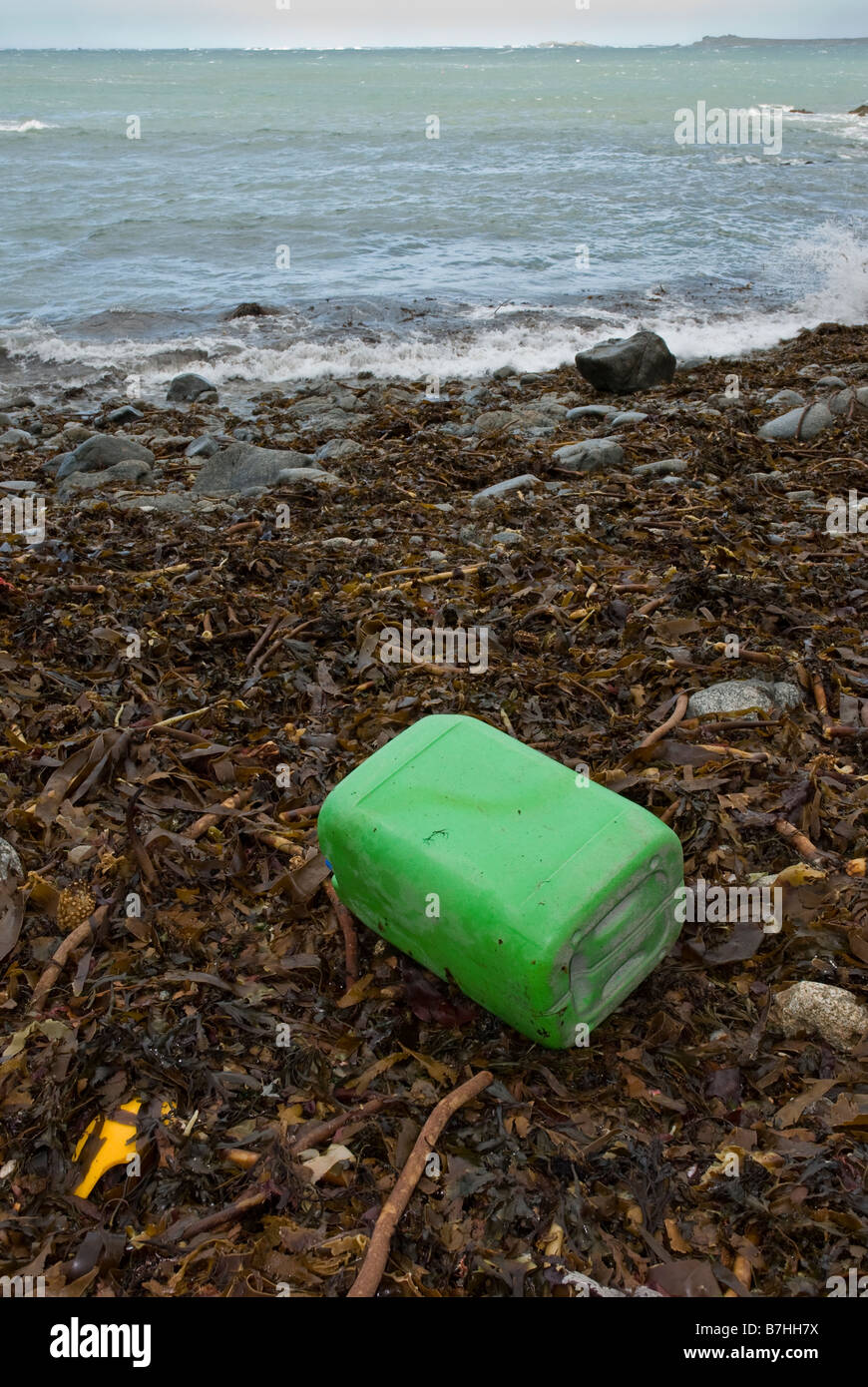 Chemical container with corrosive warning symbol washed up on seaweed covered beach. - Stock Image