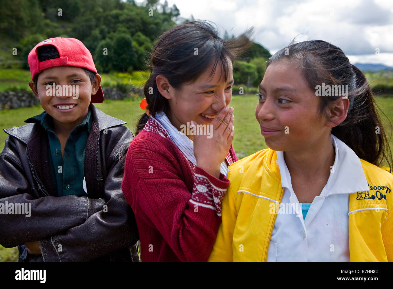Three smiling Guatemalan children pose near their church in San Nicolas Ixil Western Highlands Guatemala - Stock Image