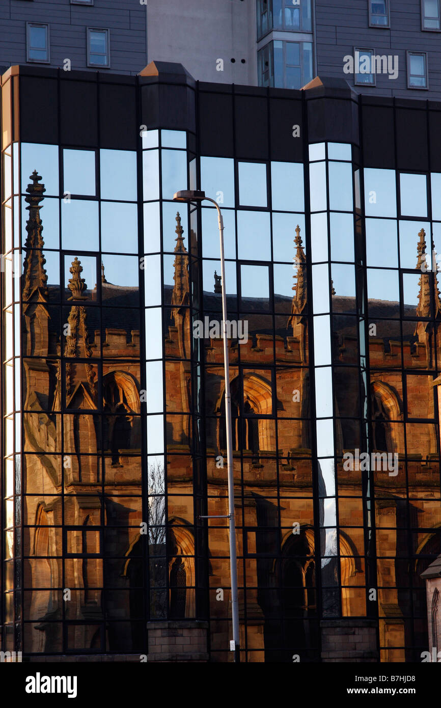 An old church reflected in modern glass office developments in central Glasgow opposite the River Clyde - Stock Image