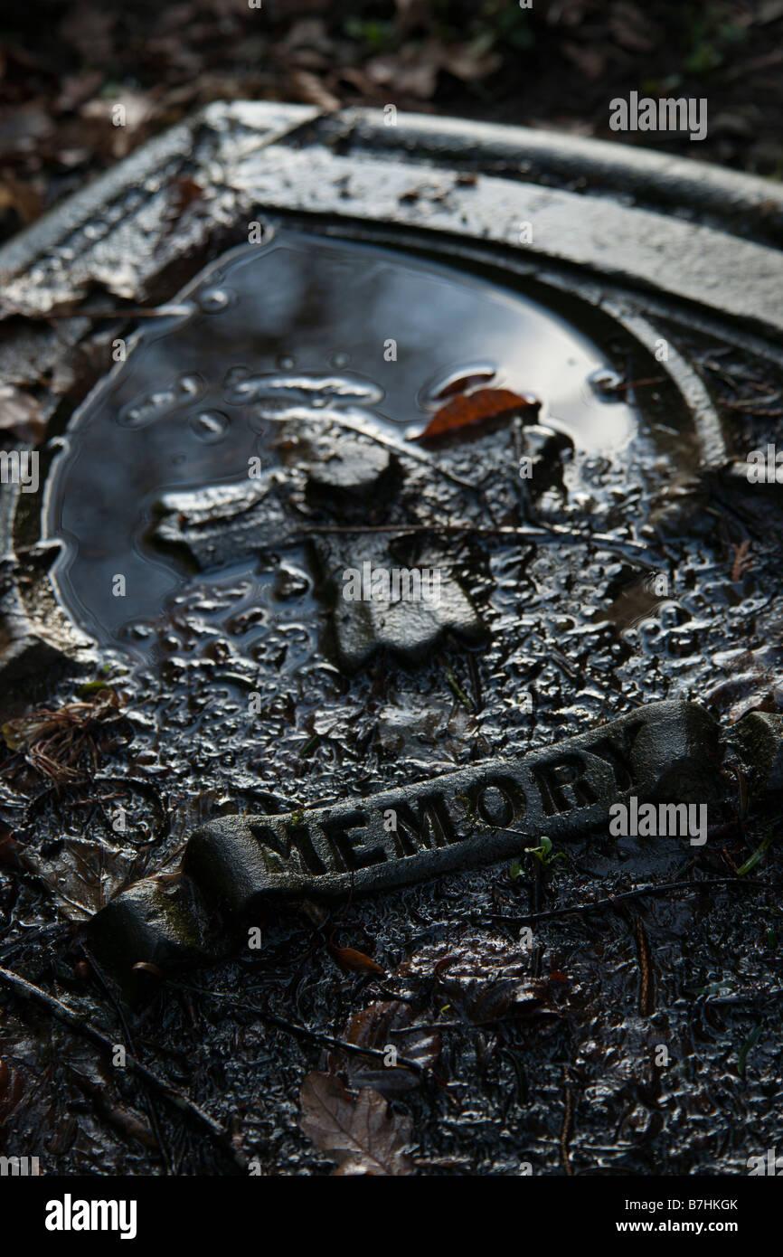 Memory a fallen gravestone in winter - Stock Image