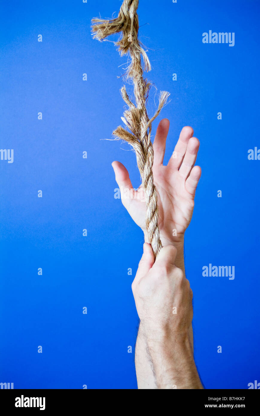 A man s hands grasping or climbing up a frayed rope portraying a very precarious situation - Stock Image