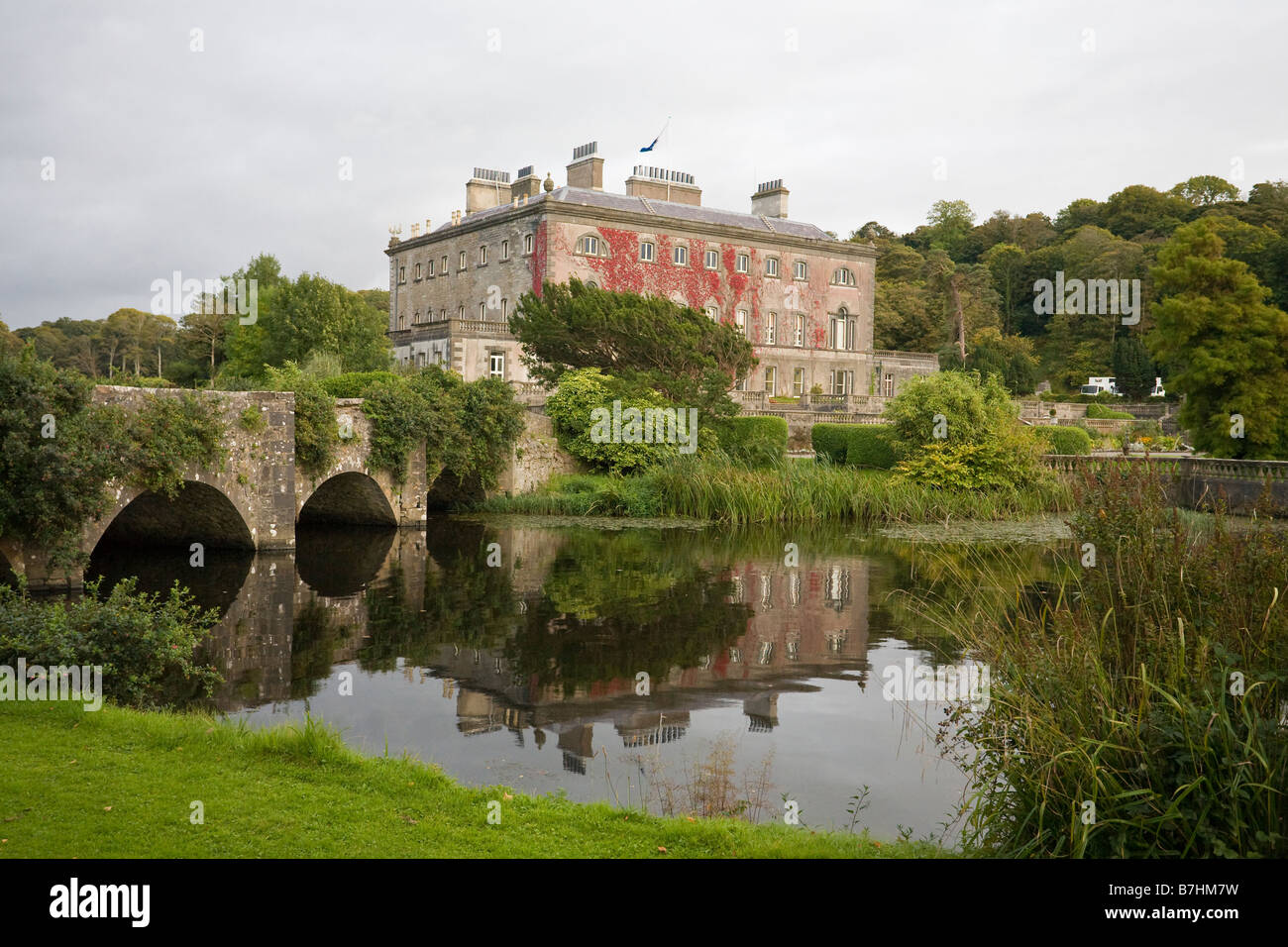Westport House and Bridge. An arched bridge leads to the red ivy covered mansion which is reflected in the front - Stock Image