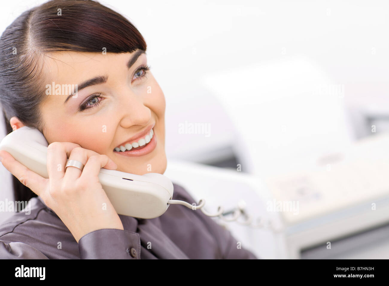 Happy Businesswoman Talking On Landline Phone In A Bright