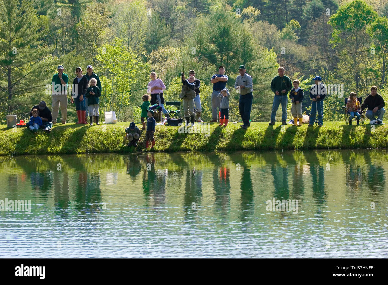 Families gathered around pond for summer morning fishing derby, reflection - Stock Image
