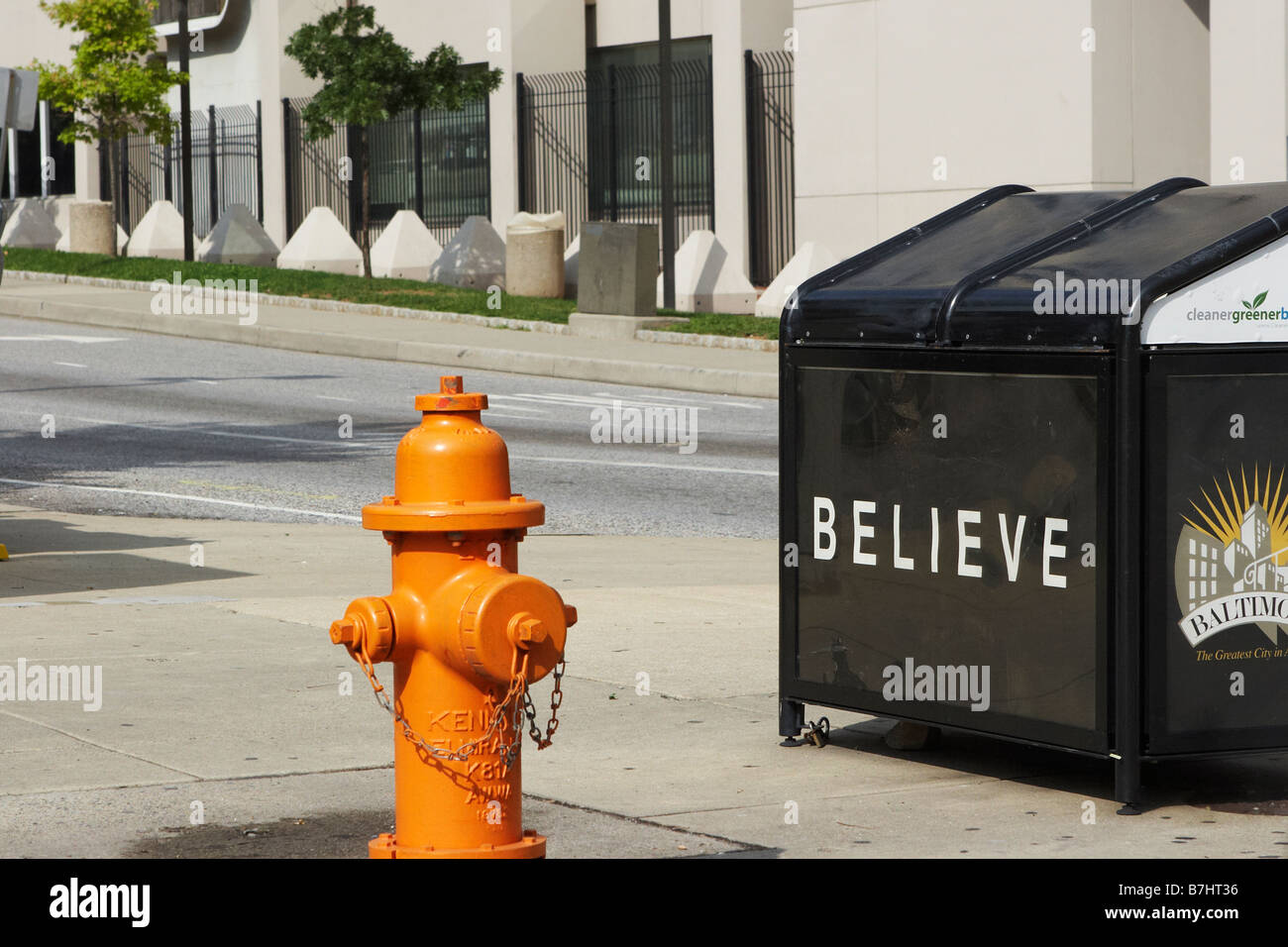 A large trash receptacle with a Believe campaign poster Baltimore Maryland - Stock Image