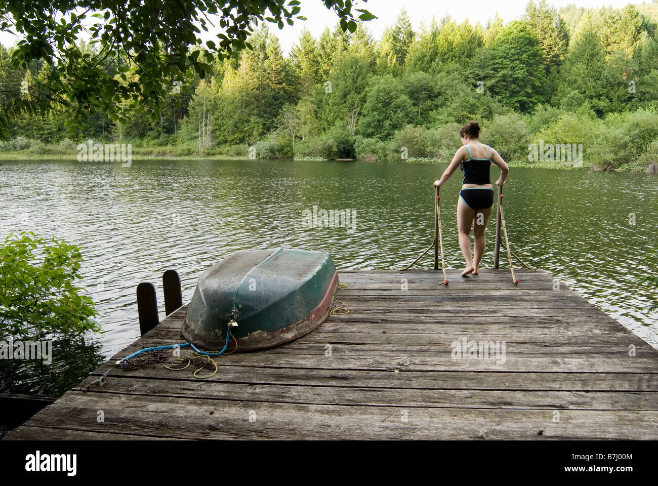 Woman (20-25) walking across a dock with a rowboat on it in a swimsuit, Victoria, Vancouver Island, B.C. Stock Photo