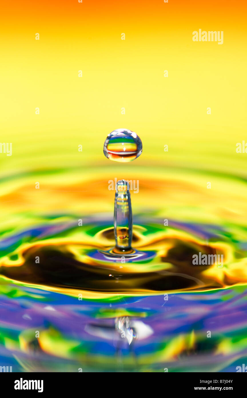 Rainbow coloured water drop and ripple - Stock Image