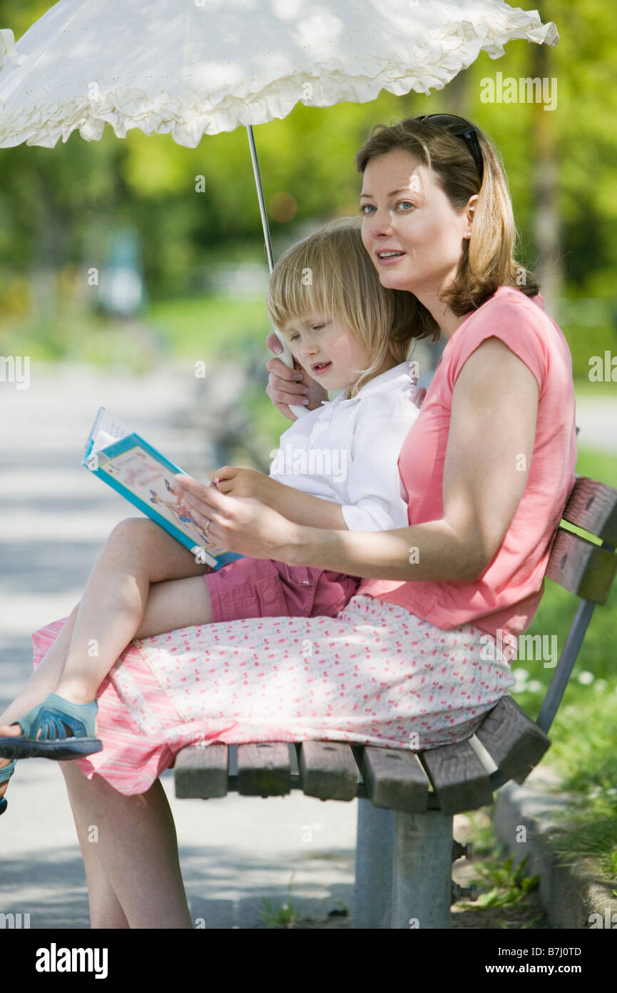 Caucasian Mom And 4 Year Old Daughter Reading A Book On A Park