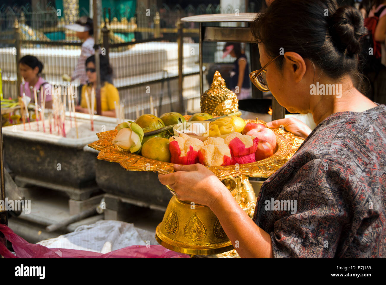 Thai woman making fruit and flower offering - Wat Phra Kaew and the Grand Palace in central Bangkok Thailand Stock Photo