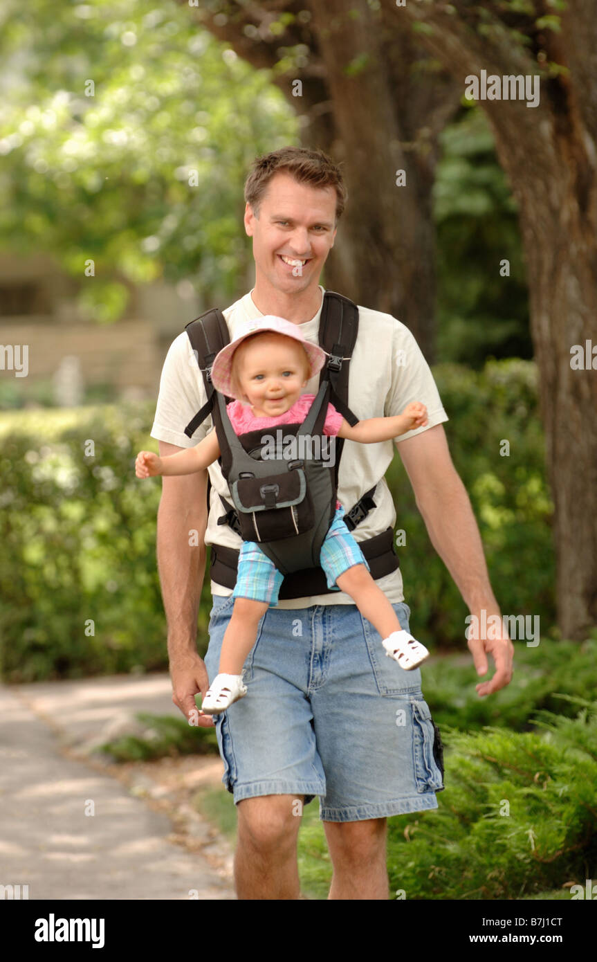 Man walking down street carrying baby in snuggly, Regina, Saskatchewan Stock Photo