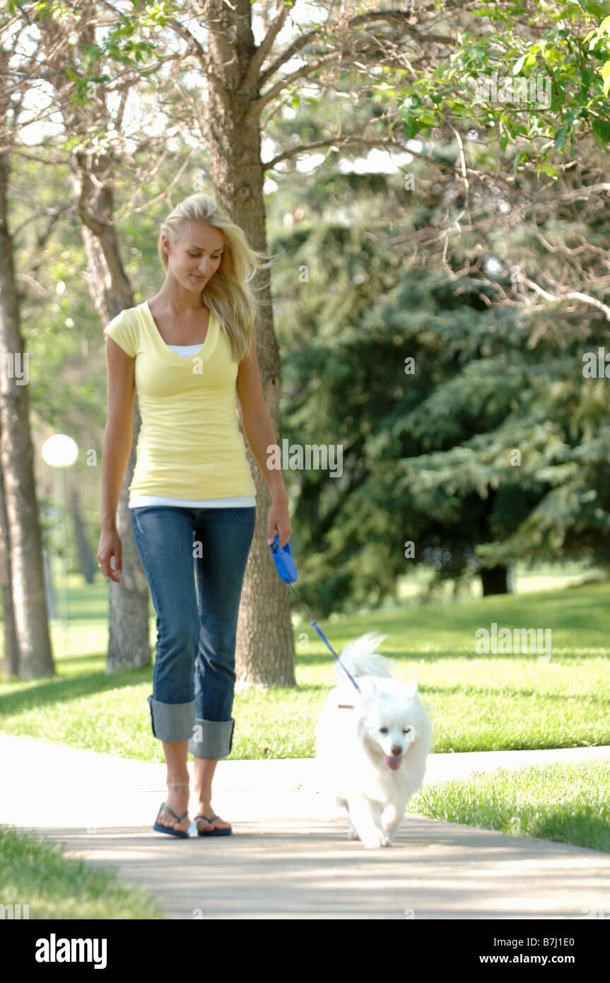 Young woman walking dog in park, Regina, Saskatchewan - Stock Image