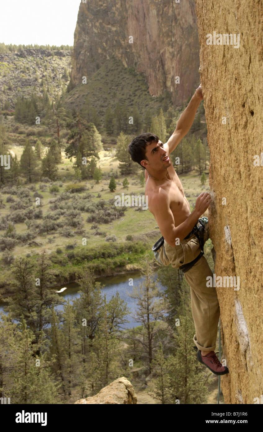 Man (25-30) clipping in to an anchor while rock climbing, Smith Rock State Park, Terrebonne, Oregon, USA - Stock Image