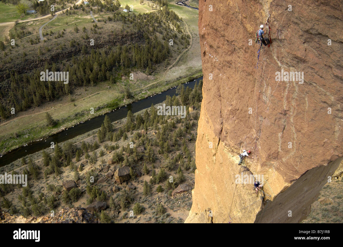 A group of men rock climbing on a free standing tower of rock., Smith Rock State Park, Terrebonne, Oregon, USA - Stock Image