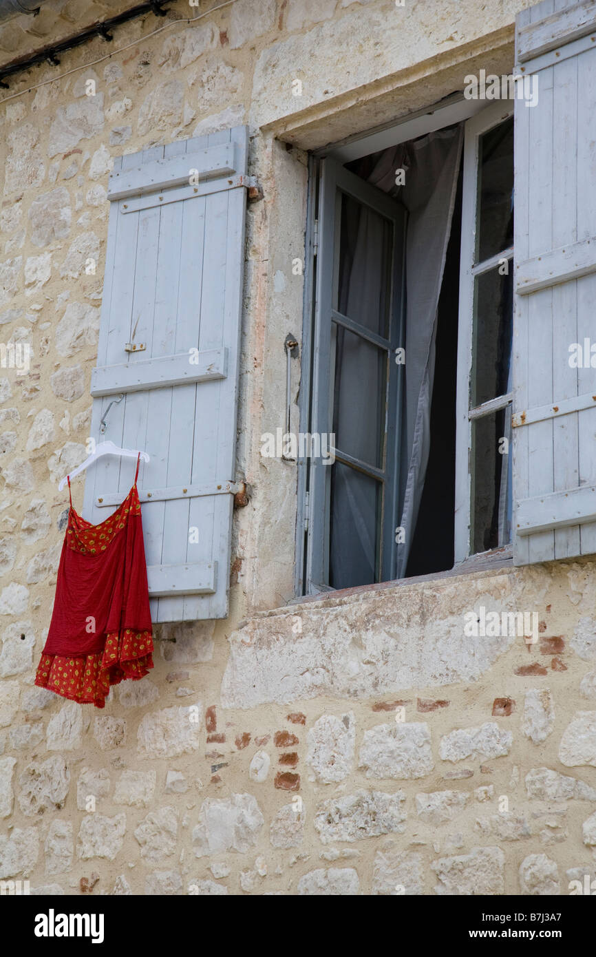 A red dress airs on a window shutter, Tournon d'Agenais, France. - Stock Image