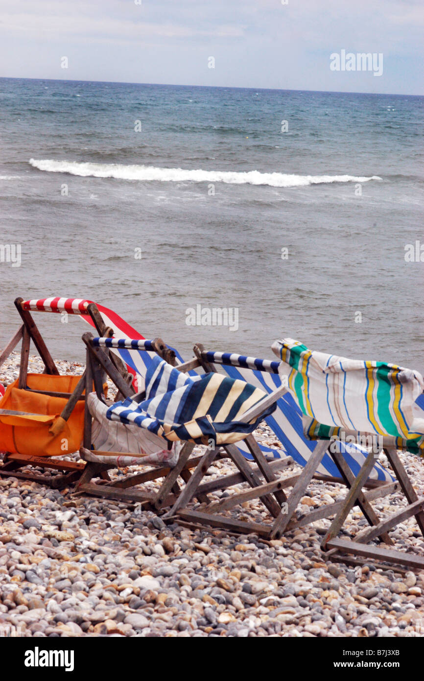 Battered deckchairs on an empty beach May Day Bank holiday Dorset UK - Stock Image